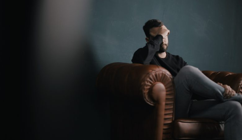 man on chair with hand over face